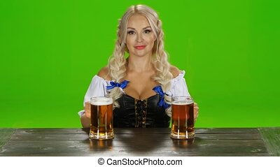 Sexy Bavarian girl sitting at a table with two glasses of beer. Green screen