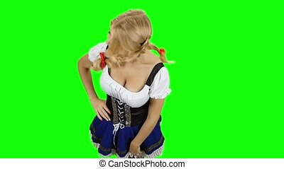 Girl in bavarian costume touches her hair and smiling. Slow...