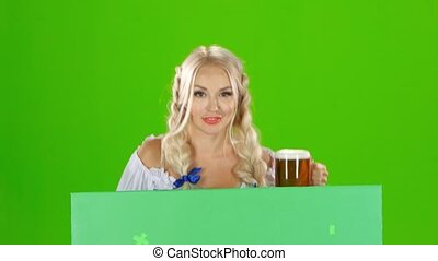 Bavarian girl looks out from behind a with a glass of beer...