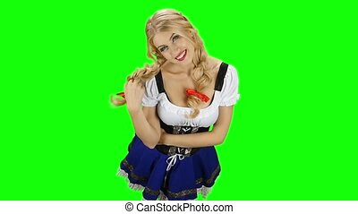 Girl in bavarian costume playing with her hair and laughs....