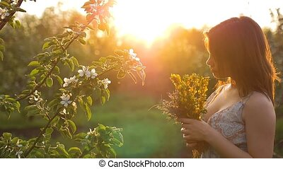 at sunset the girl smelling a bouquet of slow motion video -...