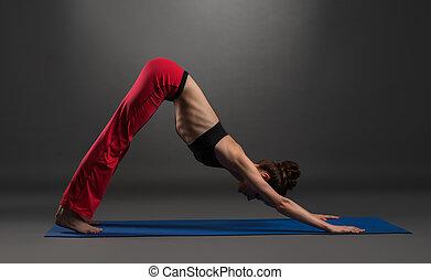 Pretty caucasian woman practising yoga in studio