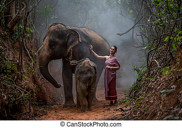 Beautiful Asian Woman wears thai dress with her elephant,...