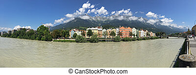 Panoramic view of colorful buildings and mountains along Inn...