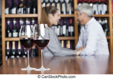 Red Wine In Glasses With Couple In Background - Closeup of...
