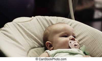 Adorable little baby sway on swing in apartment Baby dummy...