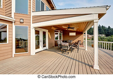 Large wooden walkout deck with flat roof extension and...