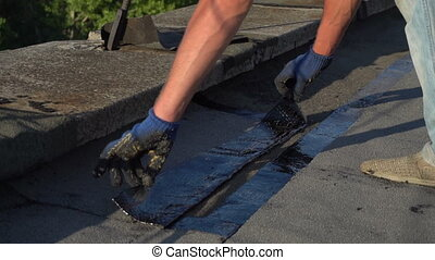 Roofer melts the bitumen - Worker repairing the roof of the...