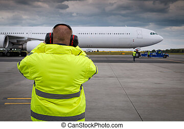 Ramp supervisor monitor situation during pushback of...