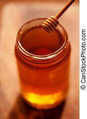 Golden Honey dipper and honey in jar on dark background...