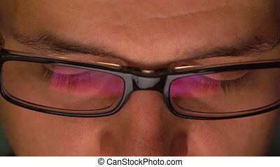 Man's dark rim glasses reflecting tablet computer in the...