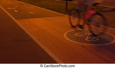 One bicycle passing by on urban bike path at night. 4K clip...