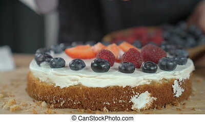 Woman cooking berry cake and decorating biscuit with...