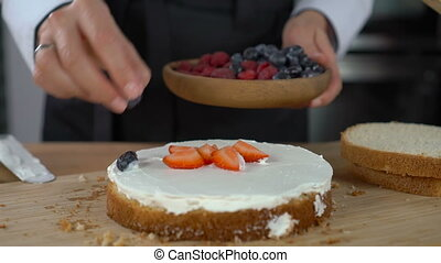 Woman cooking cake and decorating biscuit with berries -...