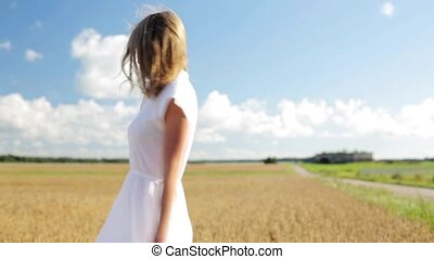smiling young woman in white dress on cereal field -...