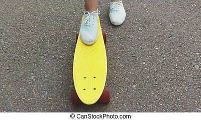 teenage girl foot putting short skateboard on end -...