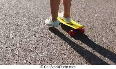 teenage girl feet riding short modern skateboard -...