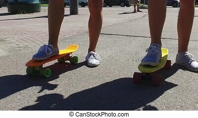 teenage couple feet riding short modern skateboard -...