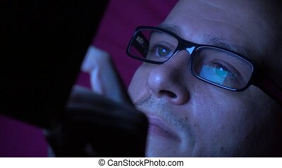 Man in black rim glasses using his tablet computer in dark...