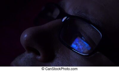Black rim glasses reflecting glowing tablet touchscreen in...