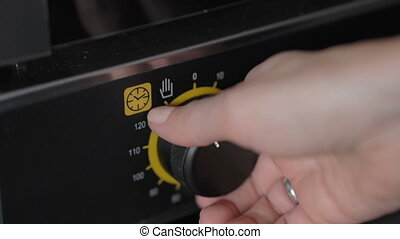 Woman hand setting temperature control on oven