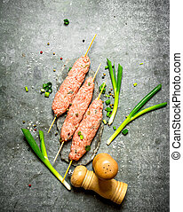 Raw kebabs on Wooden skewers with green onions On the stone...