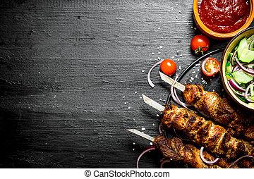 Shish kebab of pork and salad.