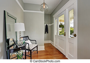 Entryway with gray walls, console table and wood floors -...
