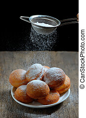 sugar with strainer over donuts - pours sugar with strainer...