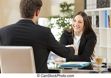 Businesspeople handshaking after negotiation or interview at...