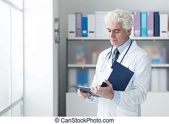 Doctor checking medical records - Confident doctor in the...