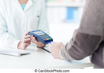 Man purchasing products in the pharmacy, he is paying with a...