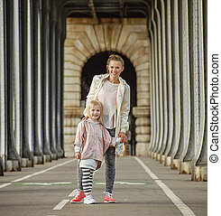 active mother and daughter standing on Pont de Bir-Hakeim...