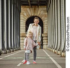 active mother and daughter standing on Pont de Bir-Hakeim...