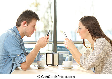 Couple on line obsessed with smart phones - Side view of a...