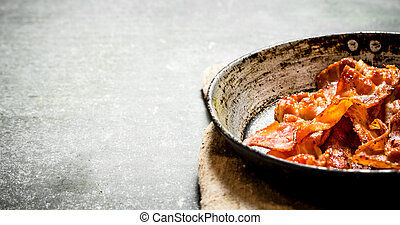 Fried bacon in a frying pan. On stone background. - Fried...