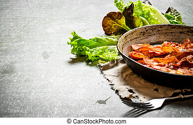 Fried bacon and greens. On stone background. - Fried bacon...