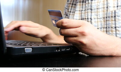 Man is using credit card and laptop for online payment. 4K...