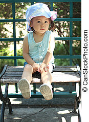 Japanese girl sitting on the bench 1 year old