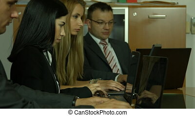 business people working on laptop - Group of four young...