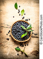 Blueberries in a Cup with leaves. On wooden table.
