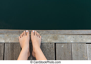 Female Feet on Wooden Deck by the Sea. Bare Woman Feet with...