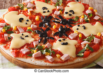 Funny pizza for Halloween with ham, cheese and vegetables...