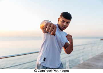 Athletic african man boxer doing boxing training on pier