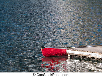 Red Canoe at Dock on quiet lake in morning sunlight