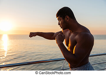 Silhouette of african man athlete practicing shadow boxing at sunrise