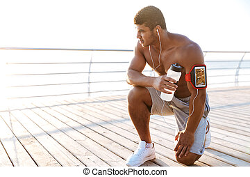 Man athlete listening to music from mobile phone in armband...