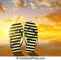 Flipflops on a sandy ocean beach at sunset. Summer vacation...