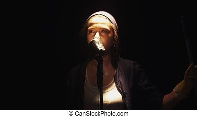 Scrubwoman with mop start sing into vintage microphone on stage of empty club