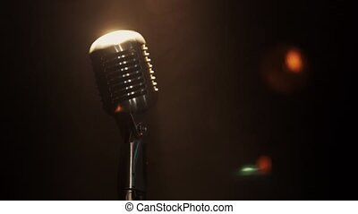 View of concert vintage microphone stay on stage under bright spotlight. Smoke.